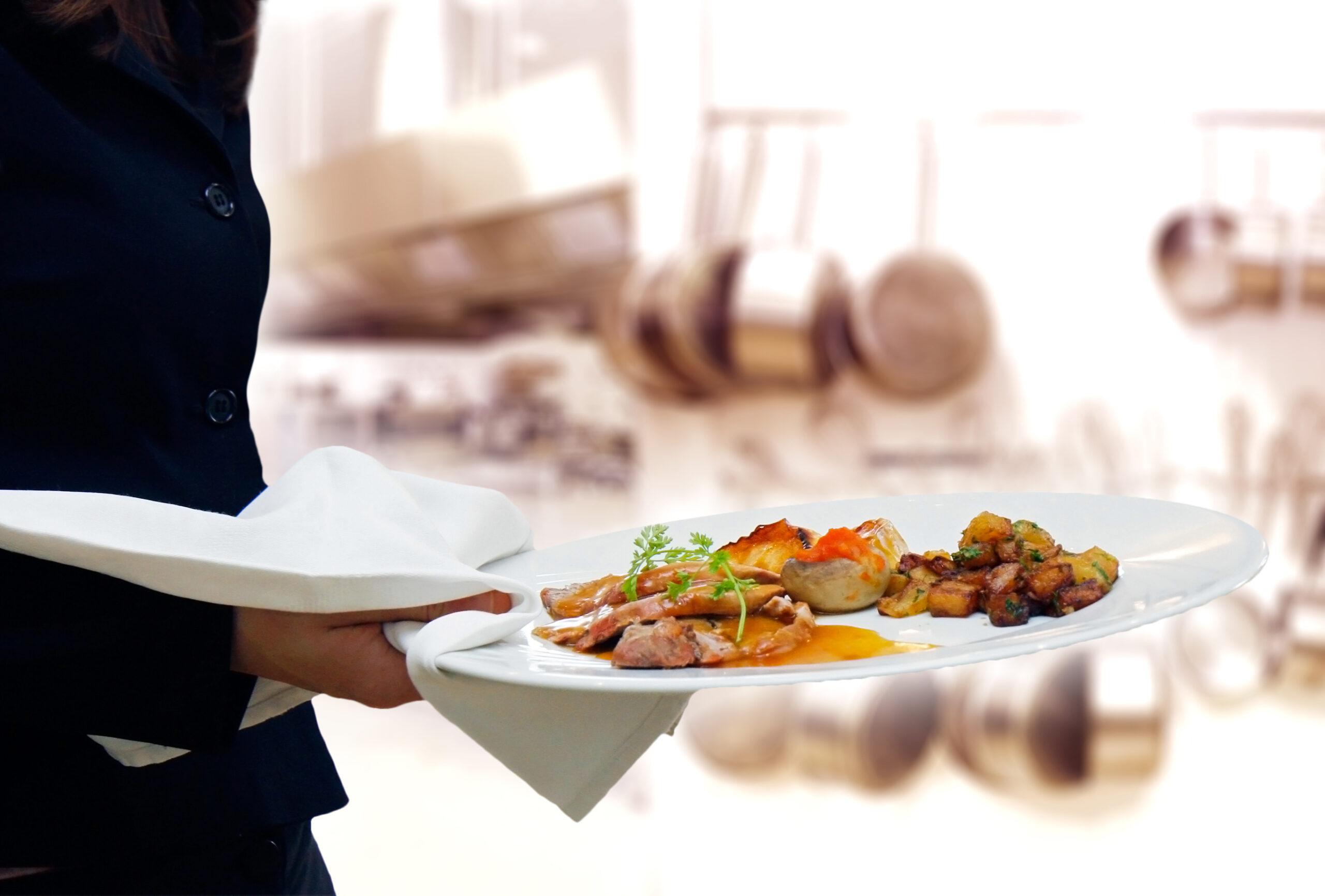 Serveringspersonal håller i tallrik md upplagd mat
