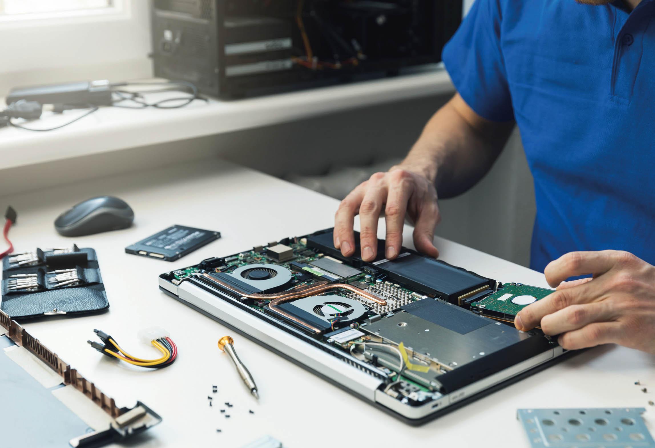 Bilden visar person som servar en laptop-dator