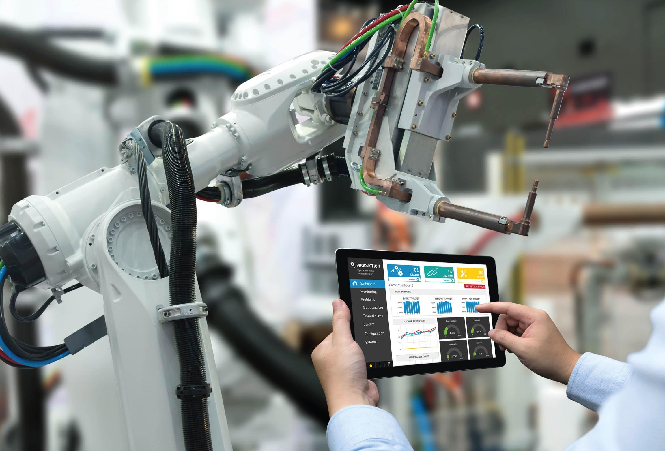 Bilden visar operatör som programmerar en industrirobot