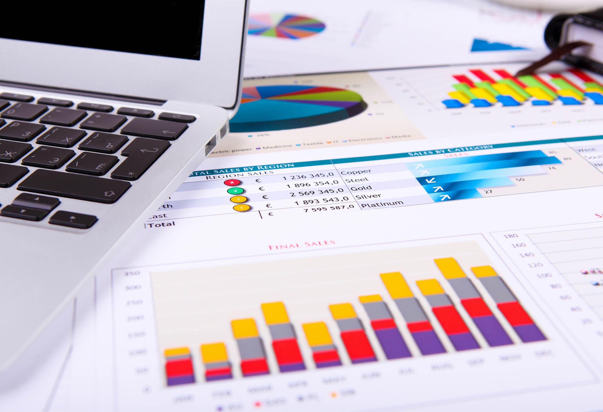 Laptop och statistikutskrifter med staplar och cirkeldiagram