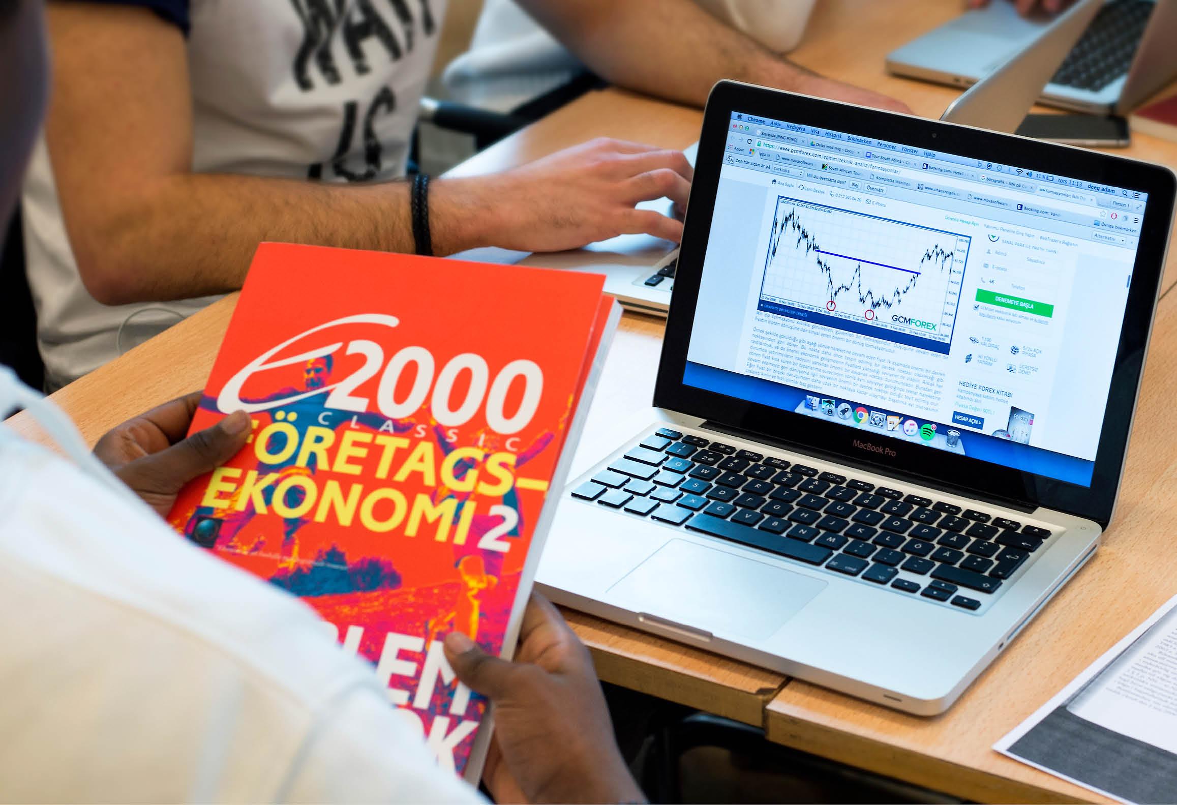 Elever som arbetar med ekonomibok och laptop