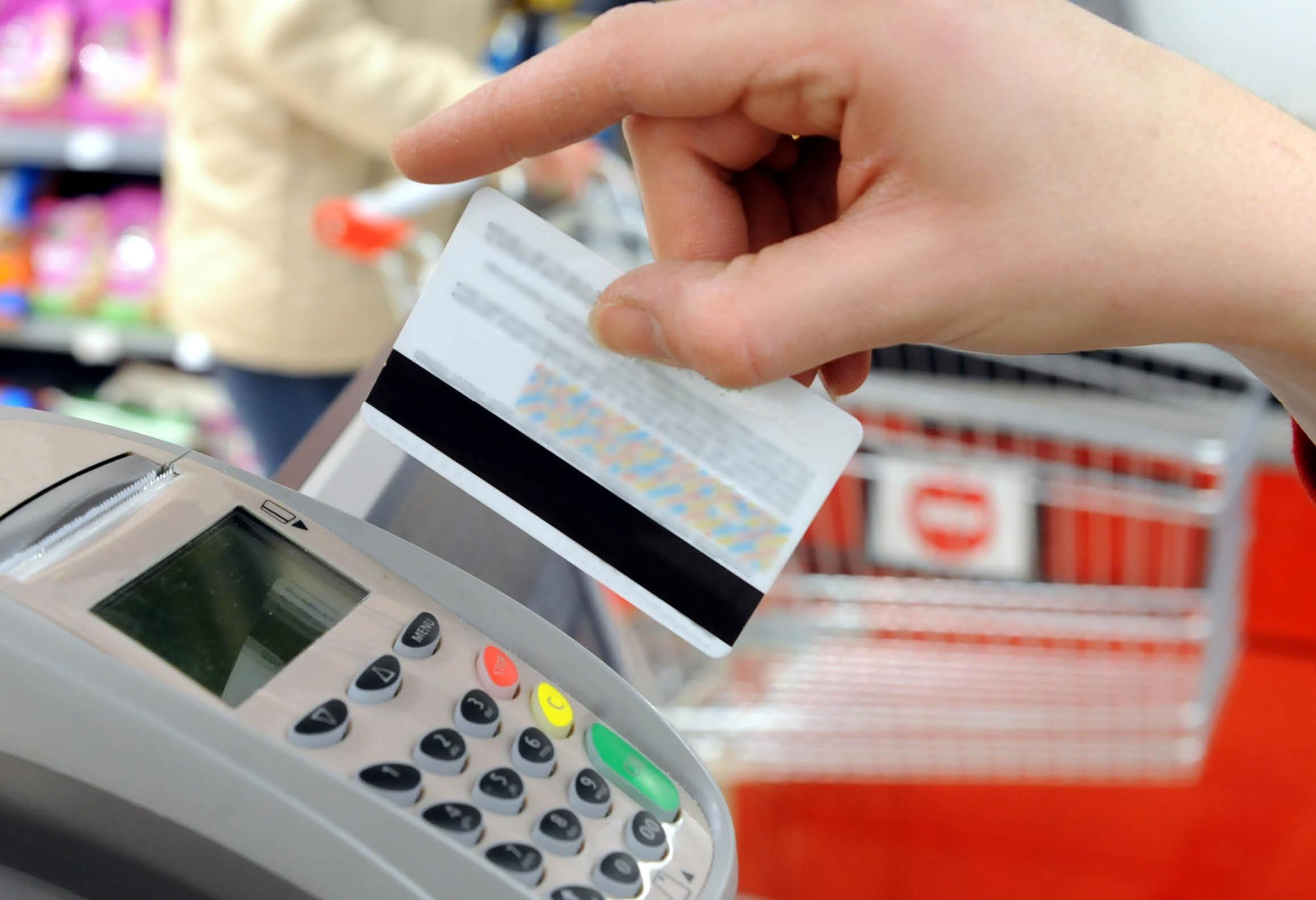 Person som drar ett betalkort i kortläsare