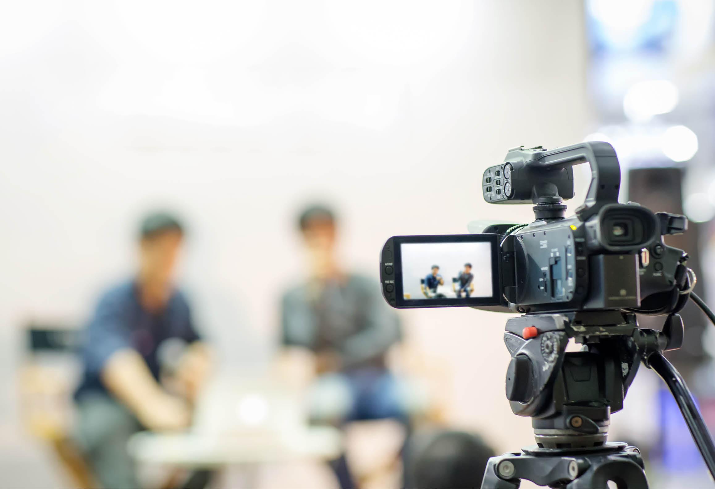Bilden visar två personer i en TV-studio som sitter framför en TV-studiokamera