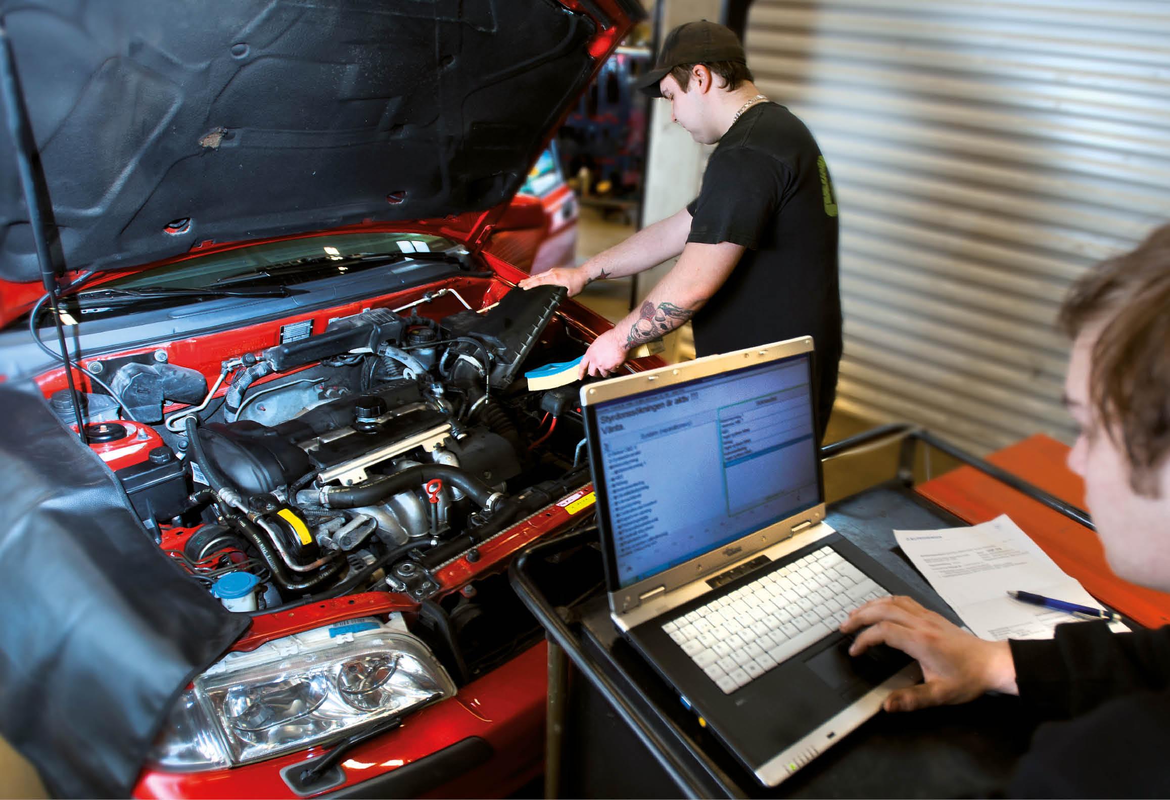 En elev arbetar med bilmotor och annan elev använder laptop