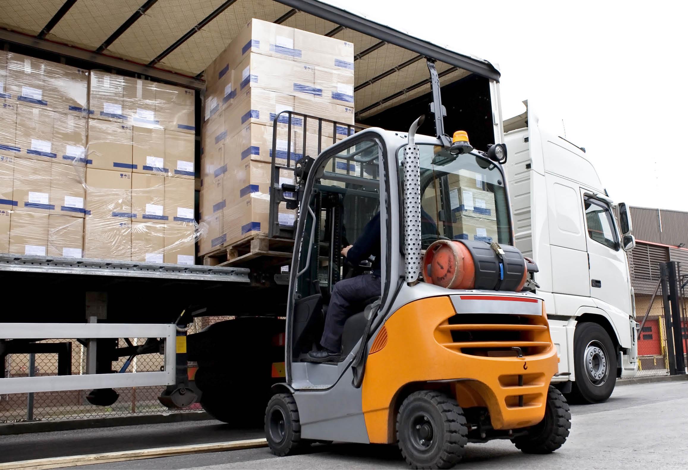 Elev kör lasttruck och hanterar gods vid lastbil