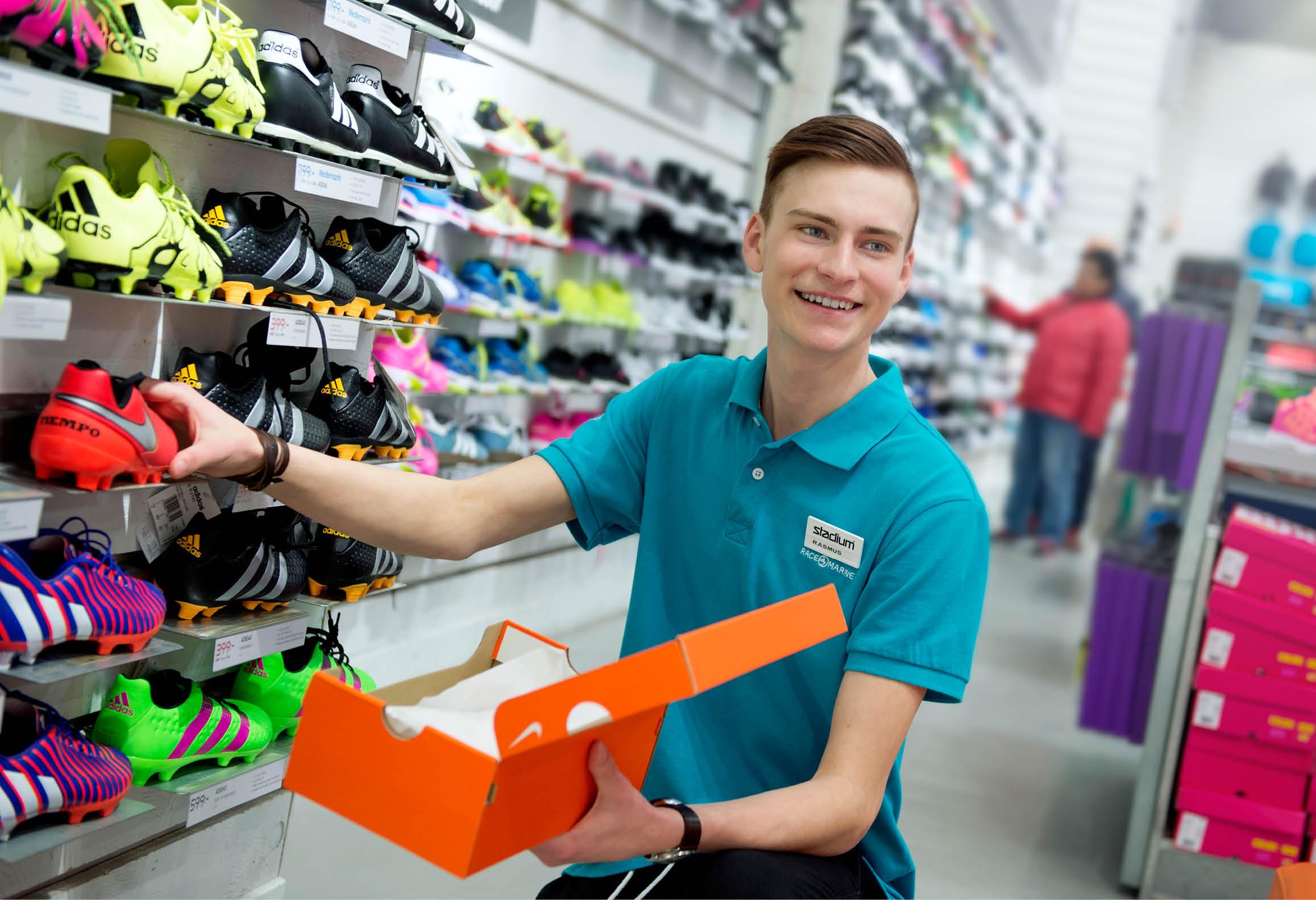 Butikssäljare i sportbutik som ställer fram fotbollsskor
