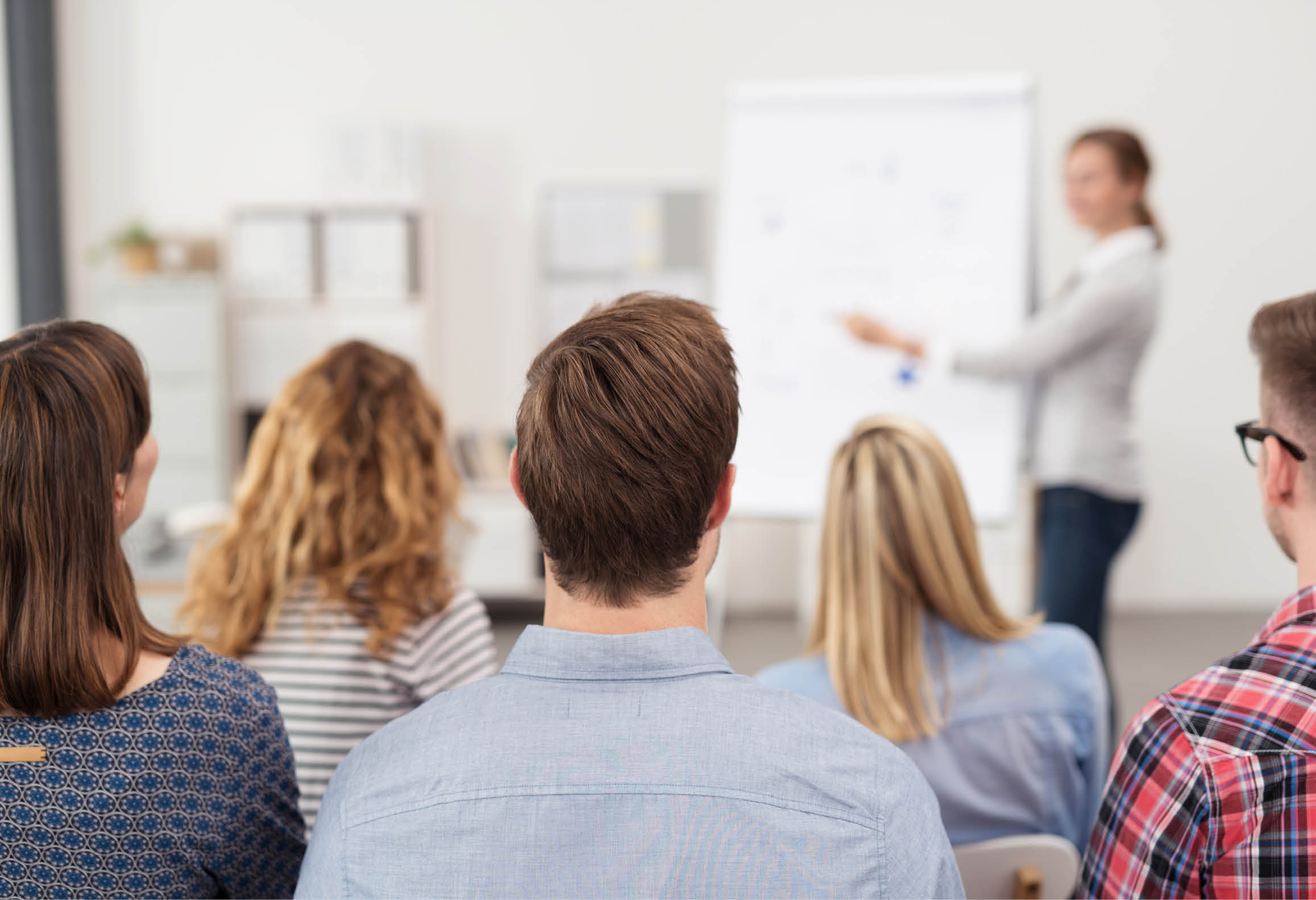 Elev presenterar vid en whiteboard framför en grupp människor