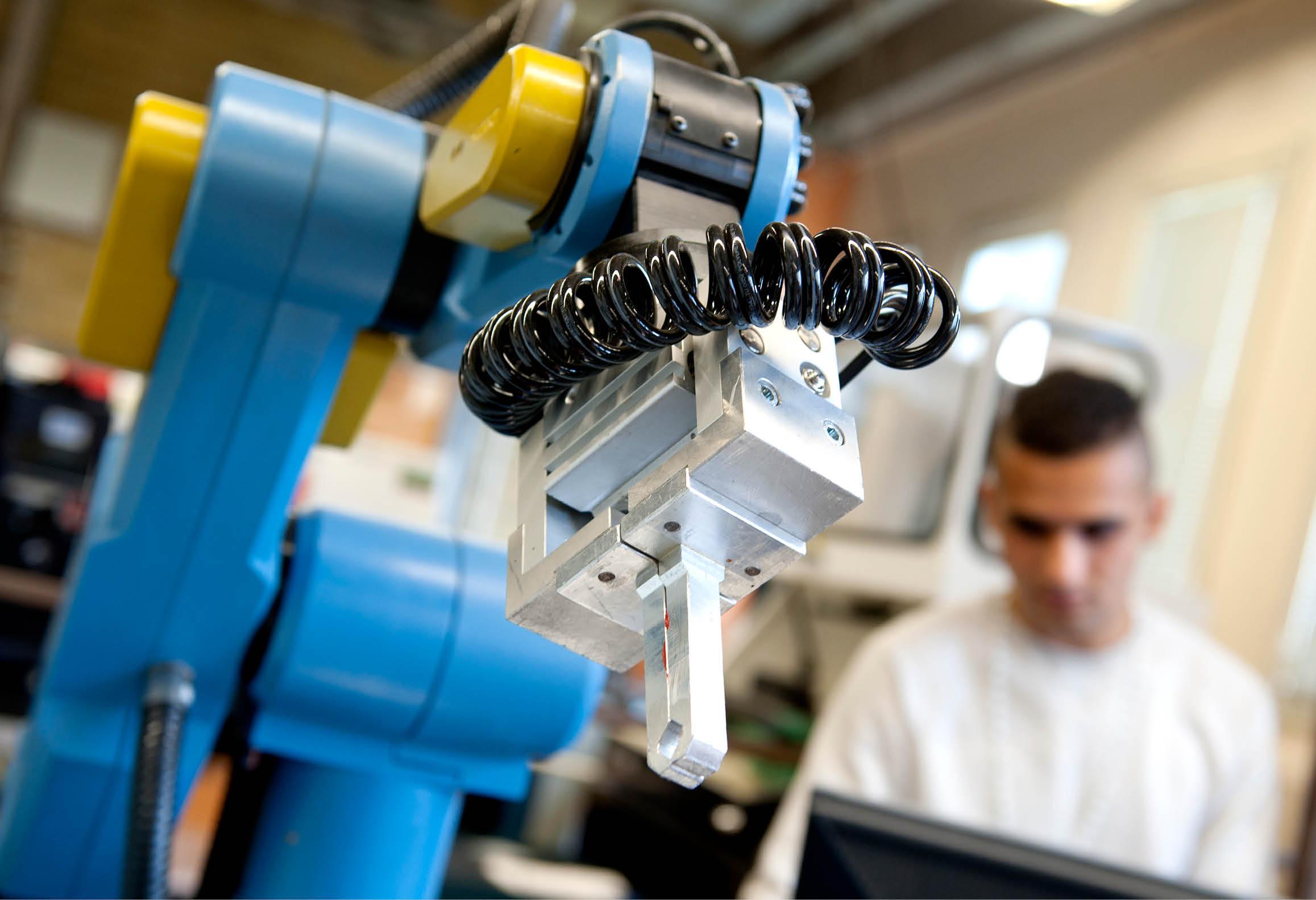 En industrirobot och en person som arbetar som operatör
