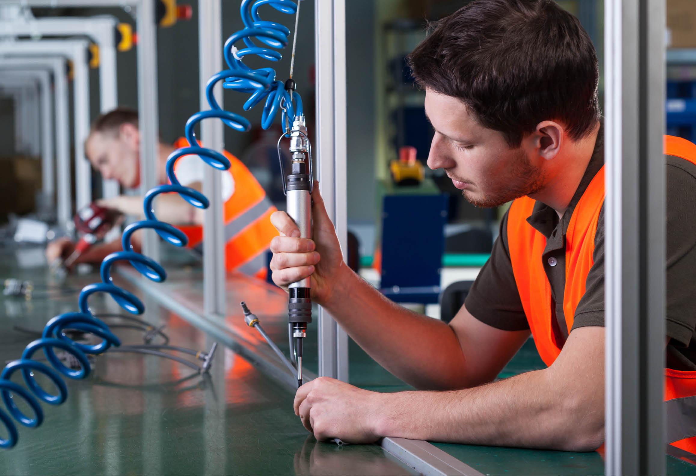 En person som monterar med hjälp av ett tryckluftsverktyg