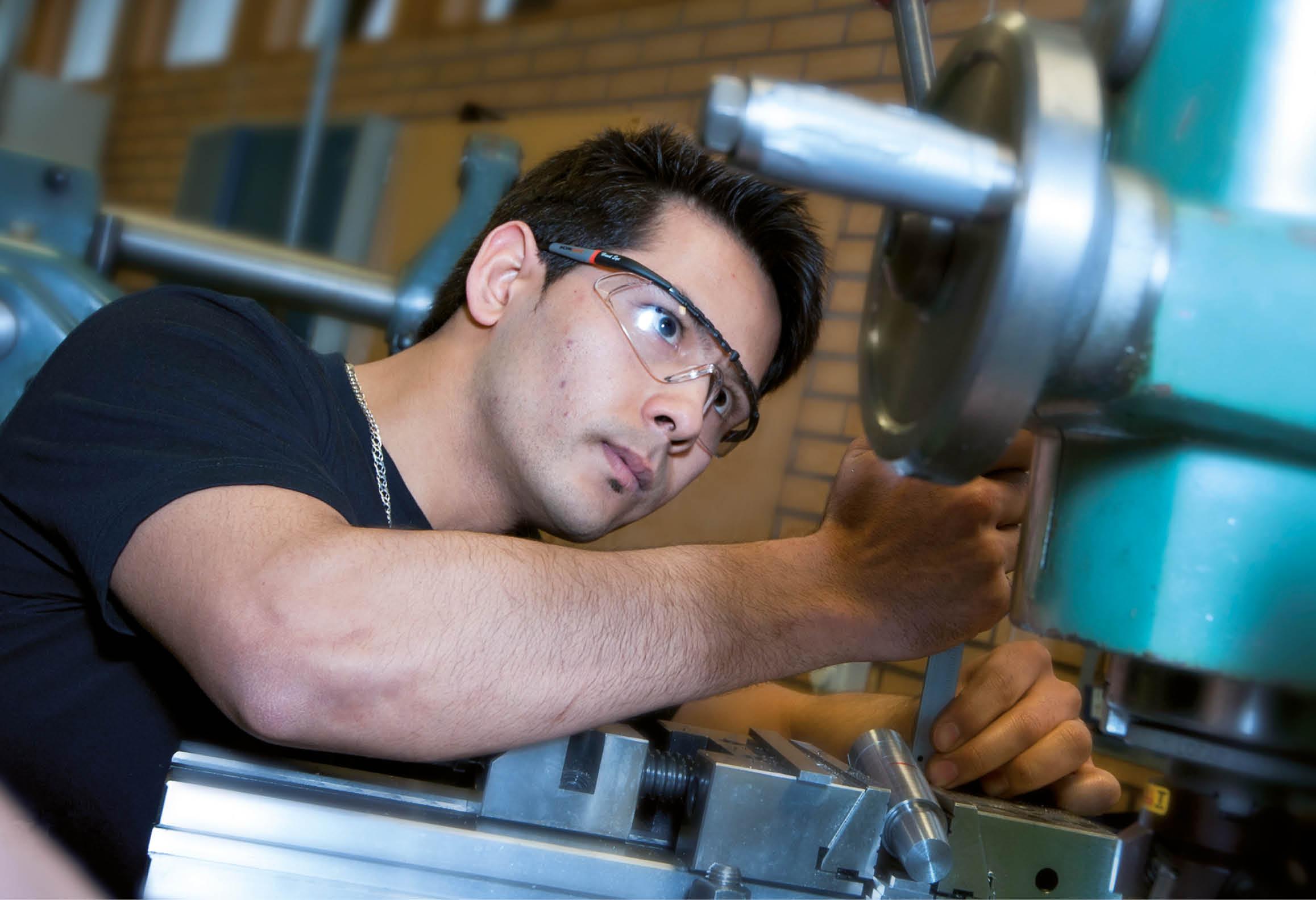 En person som kontrollmäter vid en industrimaskin