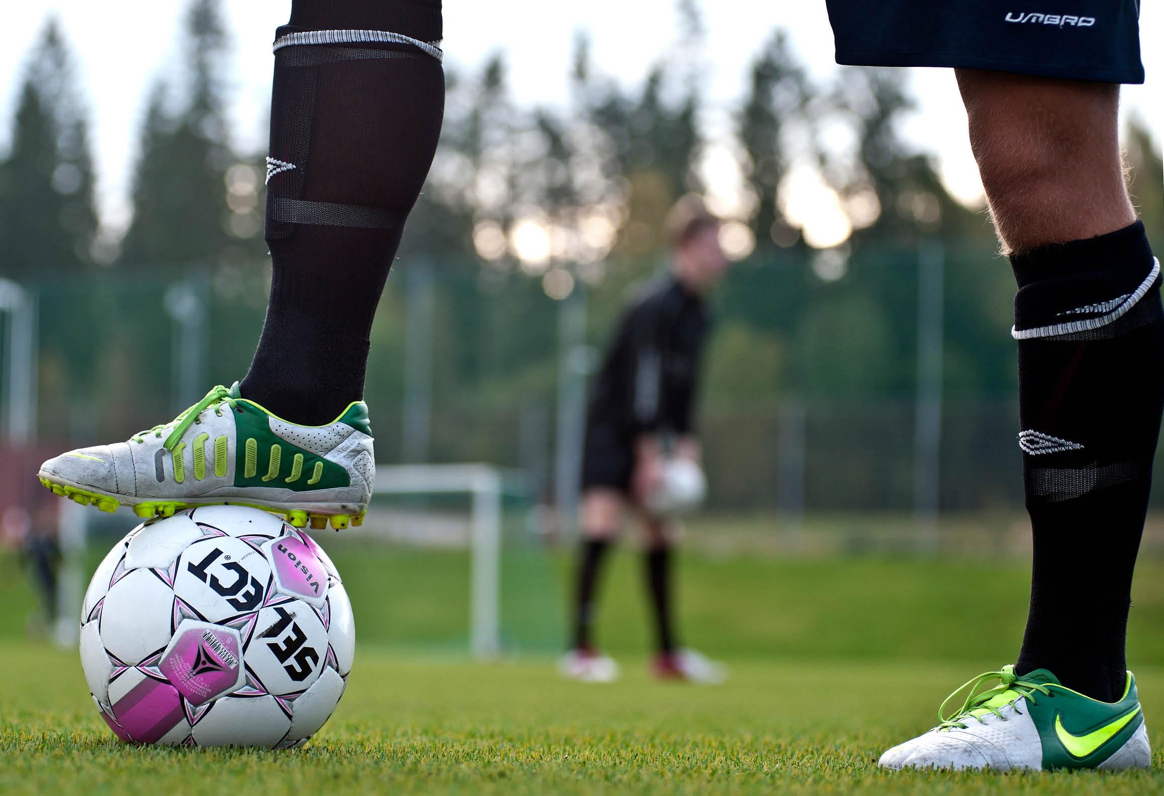 Spelare med fotboll på fotbollsplan