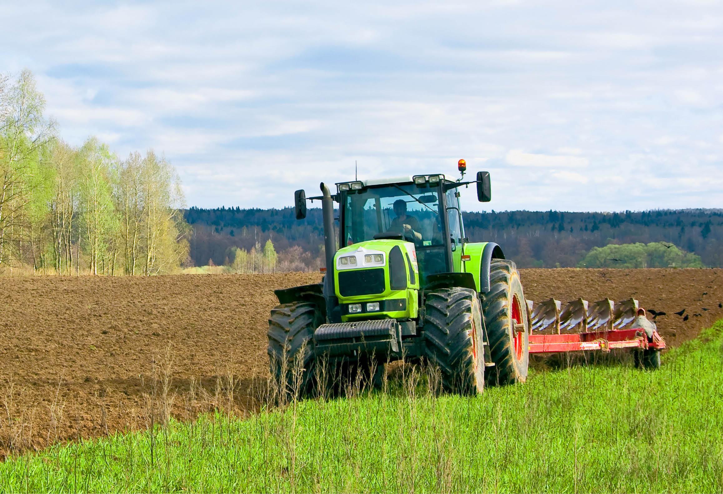 Lantbrukare som kör traktor och plöjer en åker