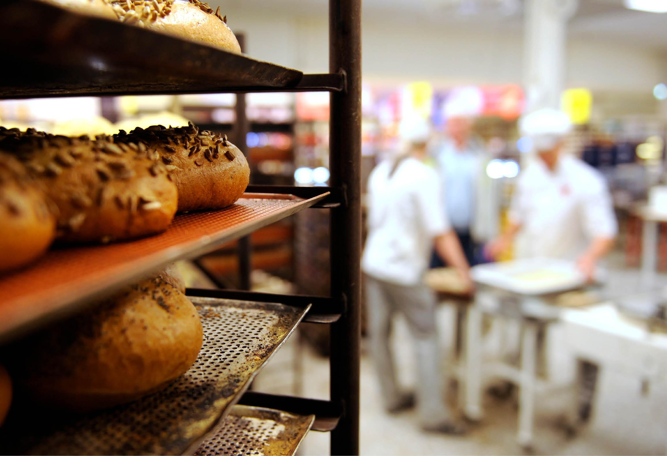 Nybakat bröd på plåt och en grupp med bagare