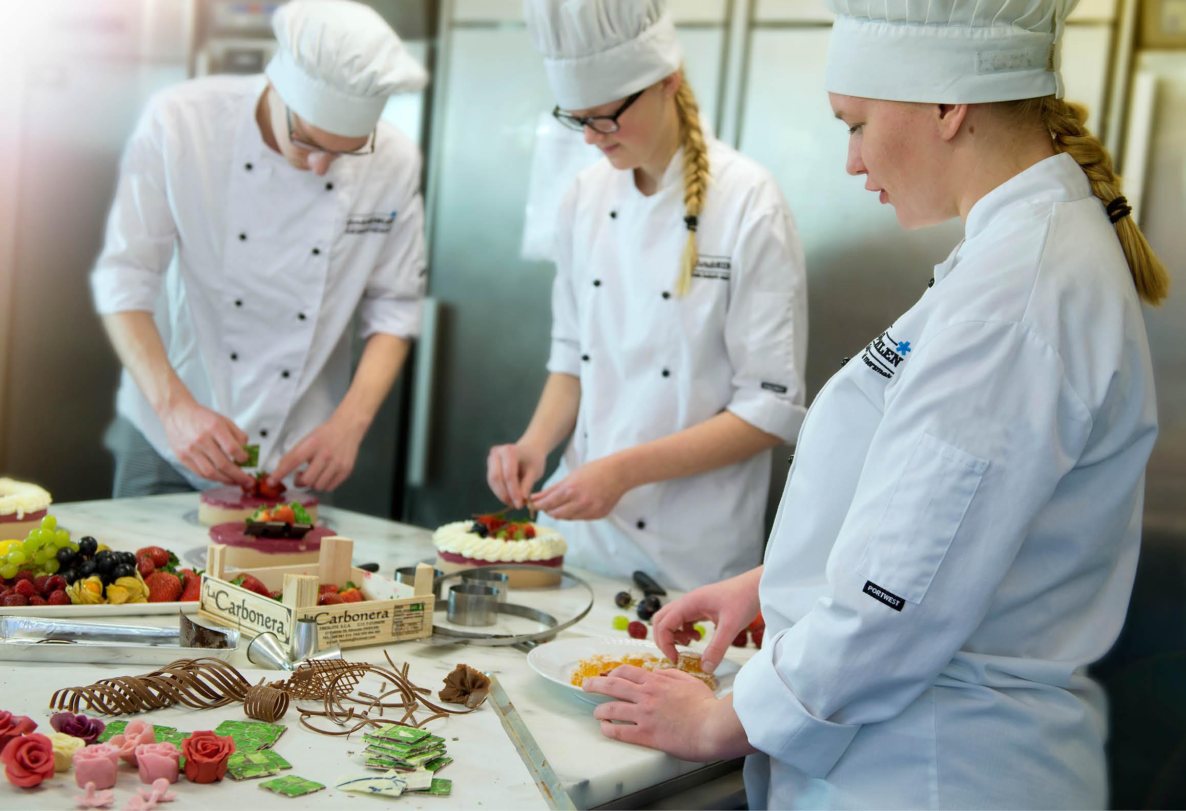 Tre konditorer som gör tårtor och andra efterrätter