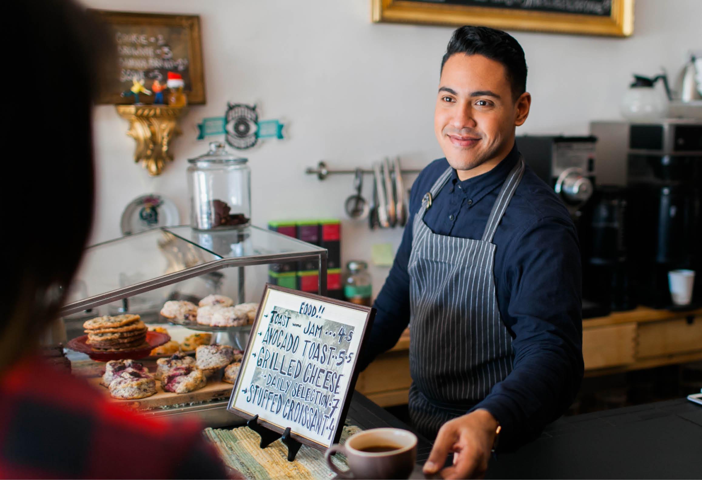 Butikssäljare på café som säljer kaffe
