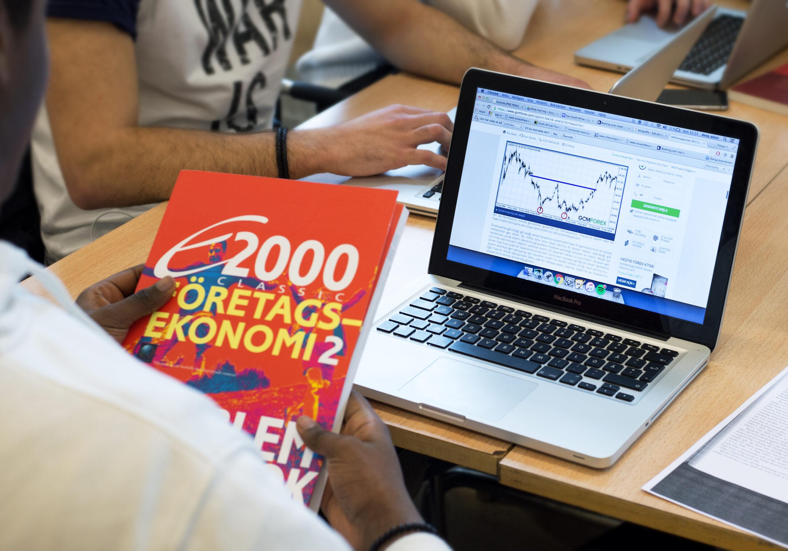 Elev med ekonomibok och skoldator