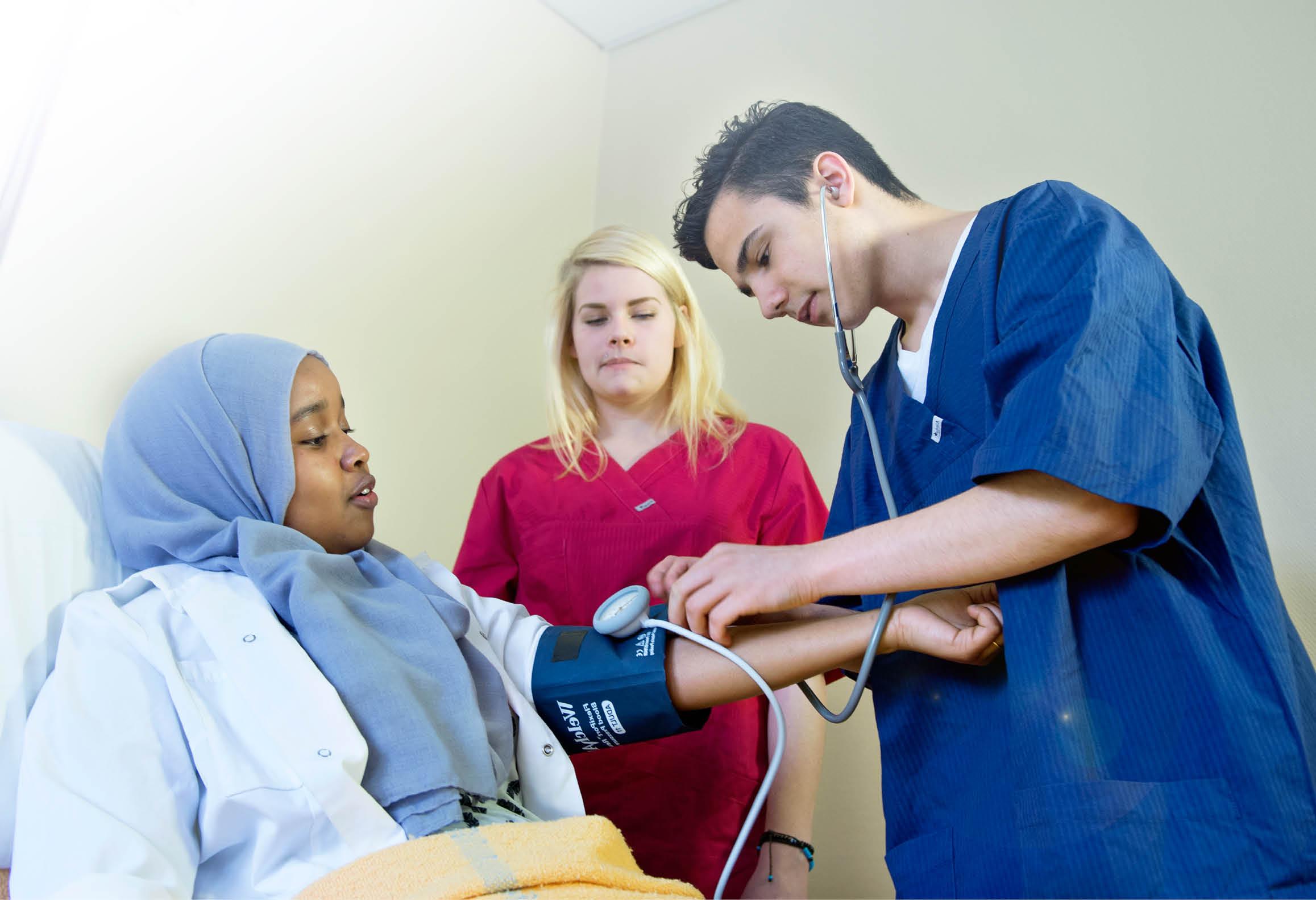 Elever övar sig i att använda blodtrycksmätare